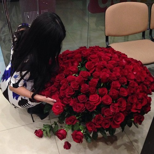 girl sitting on floor with red roses